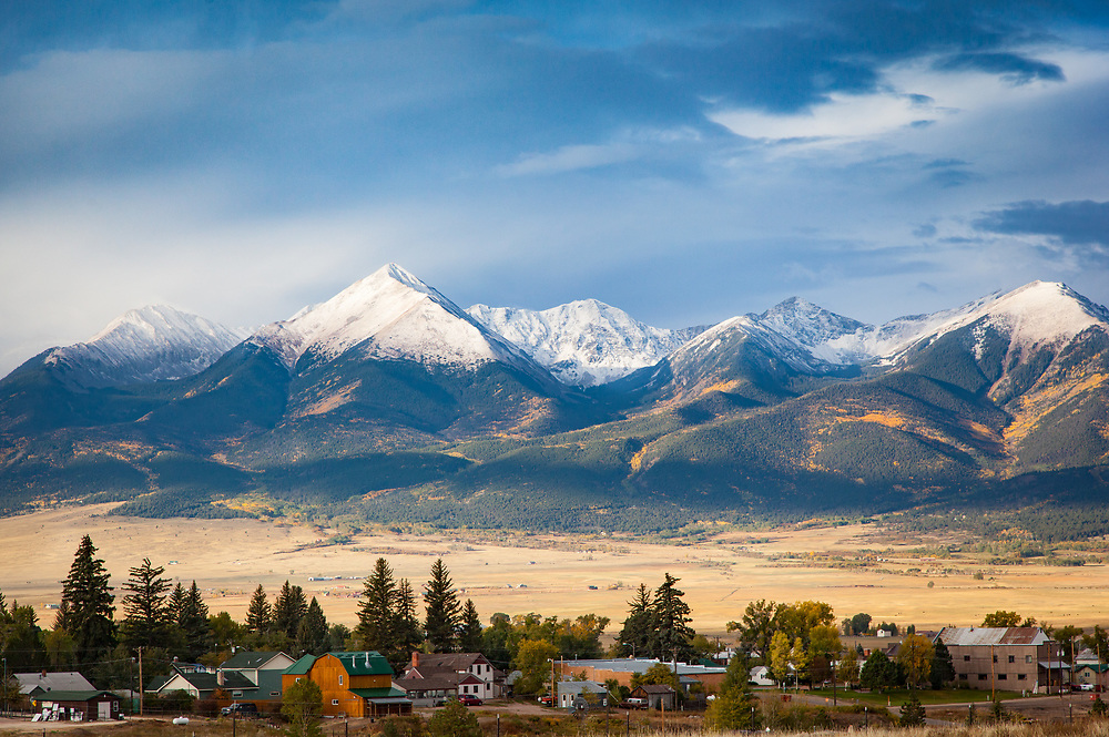 Horn Peak and the Sangre de Cristos, topped with morning clouds and fresh snow, and dressed in yellow aspens, rise over the Wet Mountain Valley and the Town of Westcliffe early on a fall morning.