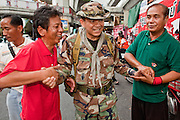 """May 12 - BANGKOK, THAILAND: Maj. Gen. KHATTIYA """"Seh Daeng"""" SAWASDIPOL (CENTER) greets civilian supporters in the Red Shirt camp in Bangkok Wednesday. Seh Daeng, as he is known, has emerged as the Red Shirts unofficial military commander. He has organized the barricades that ring the Red Shirt camp and has threatened to organize a guerilla campaign against the government if the Red Shirt protest is crushed by force. Seh Daeng is a hero to many Thais because he is credited with crushing Thailand's communist insurgency in the 1970's and 80's. He was the commander of Thailand's Internal Security Operations Command but after his political activities became apparent he was made the head aerobics instructor for the Thai army. He is now seen as one of the major personalities destabilizing the country and the government alleges that he is behind many of the grenade attacks and drive by shootings directed at government buildings and officials and he is wanted for a long list of felony offenses including weapons charges and terrorism related charges. Although some Red Shirts have officially repudiated him, he is still frequently seen around the Reds' barricades. The army has started proceedings to fire him, but he remains a general on active duty.   Photo by Jack Kurtz"""