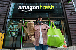 "© Licensed to London News Pictures. 16/03/2021. LONDON, UK.  A customer with his shopping outside the new 2,500 sq ft Amazon Fresh store in Wembley Park, west London on its opening day. It is the second ""just walk out"" grocery store in the UK after the opening of the Wembley branch.  As a ""contactless"" shop, it is available to anyone signed up to Amazon and with the app on their smartphone.  In-store cameras and artificial intelligence monitor customers picking up items who simply walk out and billing takes place later automatically.  Photo credit: Stephen Chung/LNP"
