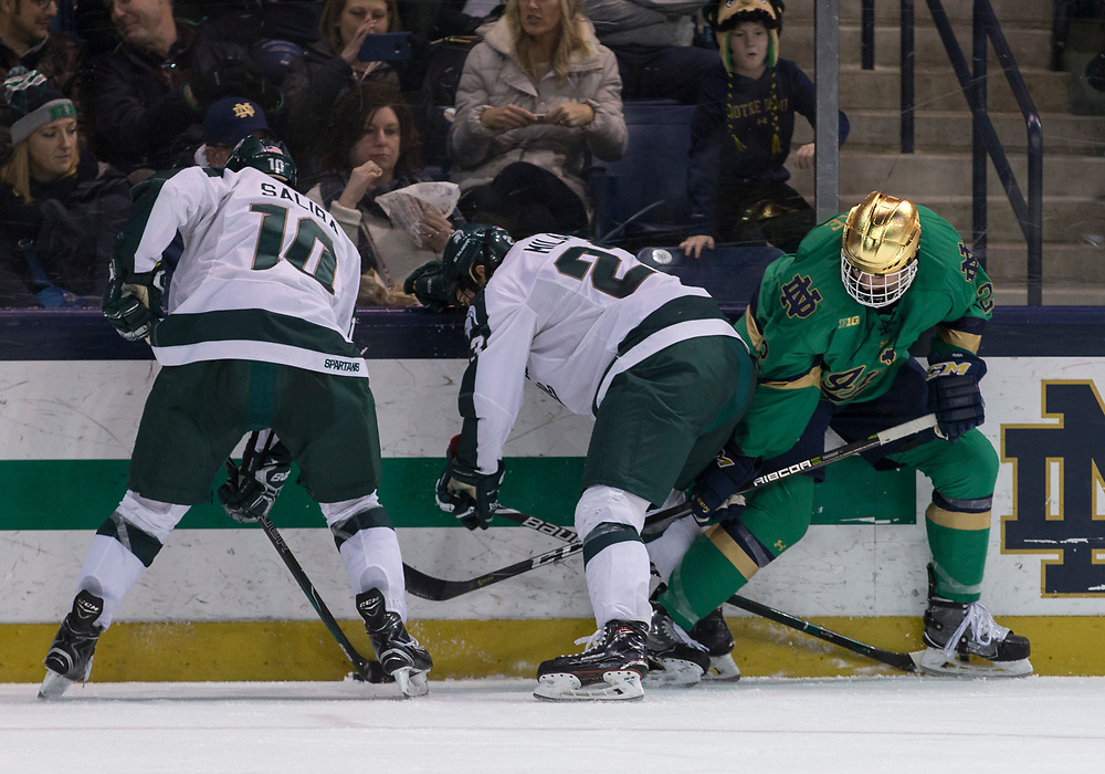 February 24, 2018:  Michigan State forward Sam Saliba (10), Michigan State forward Cody Milan (23), and Notre Dame defenseman Andrew Peeke (22) battle along the boards during NCAA Hockey game action between the Notre Dame Fighting Irish and the Michigan State Spartans at Compton Family Ice Arena in South Bend, Indiana.  John Mersits/CSM
