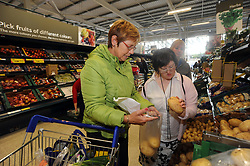 Two young women with Learning Disabilities go shopping with their support worker; Skipton; North Yorkshire, UK
