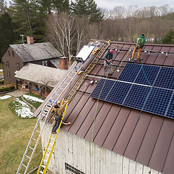 PV Squared employees installing solar panels on the roof of a barn in Shelburne, Massachusetts.