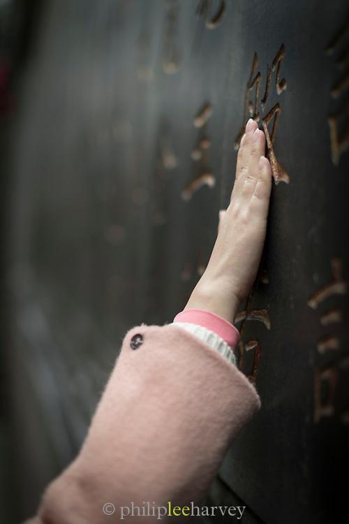 Close-up of the hand of a worshiper touching a prayer wall, Lingyin Buddhist temple, Hangzhou, Zhejiang Province, China