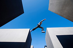 Boy jumping between concrete blocks at the Memorial to the Murdered Jews of Europe in central Berlin Germany 2008