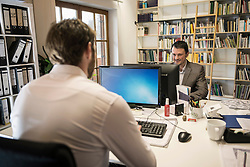 Two businessmen working on computer in an office, Bavaria, Germany