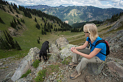 United States, Washington, Crystal Mountain, woman with black Labrador Retriever dog looking over cliff on hiking trail.  MR