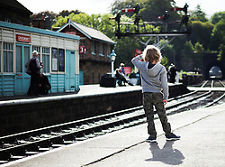 © Licensed to London News Pictures. <br /> 01/10/2016. <br /> Grosmont, UK.  <br /> <br /> A young boy stands on the edge of the platform and looks down the line from Grosmont station during the North Yorkshire Moors Railway Autumn Steam Weekend. <br /> The hugely popular railway line runs a service between Pickering and Whitby through the picturesque North yorkshire countryside and attracts thousands of visitors each year. <br /> <br /> Photo credit: Ian Forsyth/LNP