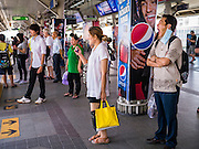 19 APRIL 2013 - BANGKOK, THAILAND:  Passengers wait for an incoming train at the Siam Station of the Skytrain also called the BTS. The system consists of 32 stations along two lines: the Sukhumvit Line running northwards and eastwards, terminating at Mo Chit and Bearing respectively, and the Silom Line which plies Silom and Sathon Roads, the Central Business District of Bangkok, terminating at the National Stadium and Wongwian Yai. The lines interchange at Siam Station and have a combined route distance of 55 km.      PHOTO BY JACK KURTZ