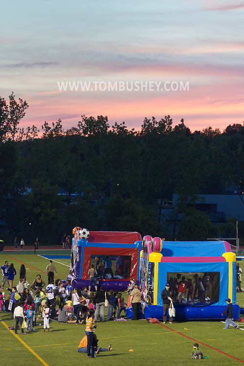 """Middletown, New York - Children wait in line to play inside bounce houses at Faller Field during Family Fun Night on May 17, 2013. After dark """"The Lorax"""" was shown on the stadium screen."""