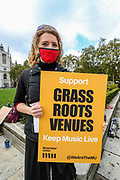 Musicians wearing face protective masks and holding placards are gathered in Parliament Gardens, outside the Houses of Commons in London, on Tuesday, Oct 6, 2020. Musicians in Britain are using their voices and instruments to protest against the government instructions to retrain and lack of support to the industry. (VXP Photo/ Vudi Xhymshiti)