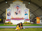 02 DECEMBER 2014 - BANGKOK, THAILAND: A woman shares a bottle of water with her daughter before the Trooping of the Colors military parade on Sanam Luang in Bangkok. The Thai Royal Guards parade, also known as Trooping of the Colors, occurs every December 2 in celebration of the birthday of Bhumibol Adulyadej, the King of Thailand. The Royal Guards of the Royal Thai Armed Forces perform a military parade and pledge loyalty to the monarch. Historically, the venue has been the Royal Plaza in front of the Dusit Palace and the Ananta Samakhom Throne Hall. This year it was held on Sanam Luang in front of the Grand Palace.    PHOTO BY JACK KURTZ