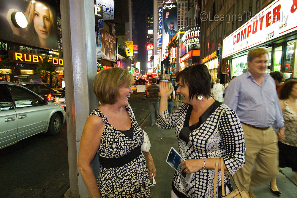 Carol and Pam wait for a taxi after the theatre on Broadway, with Times Square in the background, New York City, NY, USA