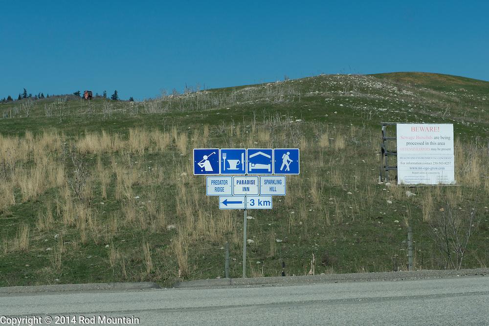 Signs along an Okanagan road point the way to Predator Ridge Golf, Paradise Inn and Sparkling Hill Resort.