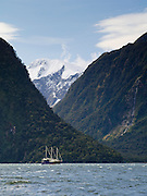 View of a Real Journeys' Overnight Cruise boat on Milford Sound, with Mount Pembroke in the background; Milford Sound, Fiordlands National Park, New Zealand