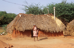 Woman standing outside a hut in a village in Tamil Nadu; India,
