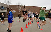 Coach Joan Forge works the Gilford High School softball team through conditioning drills with Maddie Harris leading the pack during their Friday afternoon practice session.  (Karen Bobotas/for the Laconia Daily Sun)
