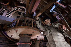 """Jaap Bes is the head volunteer miller at the De Ster Snuff and Spice mill in Rotterdam, The Netherlands. Bes checks the machinery hidden in the """"cap,"""" or the very top of the mill, where the main mill shaft is connected to the wings. The top of the mill can rotate 360 degrees to catch the wind from any direction. (Photo © Jock Fistick)"""