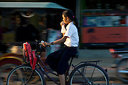 A schol girl cycles through the streets of Siem Reap, Cambodia