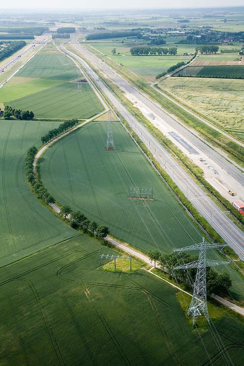 Nederland, Gelderland, Valburg-Elst, 28-06-2006; spooremplacement Betuweroute: links het hoofdspoor van de goederenspoorlijn (naar het Westen, richting haven Rotterdam), rechts hiervan de opstelsporen die onderdeel uitmaken van het het  Container Uitwissel Punt (CUP) wat gebruikt zal worden voor de overslag van containers; goed te zien is wat de lokale gevolgen zijn van de aanleg van de goederenspoorlijn: de lokale weg is doorsneden; linksboven de autosnelweg A15; op deze lokatie zou in de toekomst het multimodaal transport centrum (MTC) gebouwd moeten worden; vrachtvervoer, milieu, transport, infrastructuur, infrabundel, verkeer en vervoer, goederen spoorlijn, mobiliteit, planologie. hoogspaiingsmasten, elektricteit-koppelnet; ook (lucht)foto's van de bouwfase en andere (lucht)foto's van deze lokatie; deel van de serie Panorama Nederland luchtfoto (toeslag aerial photo (additional fee required .foto Siebe Swart / photo Siebe Swart