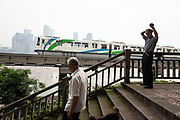 A CRT Chongqing Rapid Transit monorail train moves along the banks of the Jialing River and past an elderly man doing his morning exercises in Chongqing, China, on Tuesday, May 31, 2016. The municipality of 30 million peoples state-led development approach fueled growth of 11 percent last year, the fastest pace nationwide, with President Xi Jinping praising policy innovations that have included subsidized housing and relaxed residency rules that encourage labor mobility.