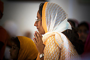 12 AUGUST 2012 - PHOENIX, AZ:  A woman prays during Sunday services at the Guru Nank Dwara Ashram Sikh temple in central Phoenix. Guru Nank Dwara Ashram is the oldest of three Sikh temples in the Phoenix area. There are about 1,500 Sikh families in the area. Memorials have been held throughout the week to honor the Sikhs killed in the mass shooting in Wisconsin last week. Sunday's service included several mentions of the massacre and was attended by a number of people active in the Phoenix interfaith community.   PHOTO BY JACK KURTZ