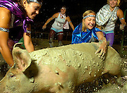 NEWS&GUIDE PHOTO / PRICE CHAMBERS.The pig wrestling event on Wednesday night at the Teton County Fair drew 60 teams with a dream of grabbing the mud covered hog and stuffing it in the barrel. These four girls comprise the Swinetastic 4, and were unable to subdue the slippery animal. From left to right: Natalie Dahlin, Lindsay Long, Lindsey Primich and Jessica Spangler chase the muddy pig in vain.