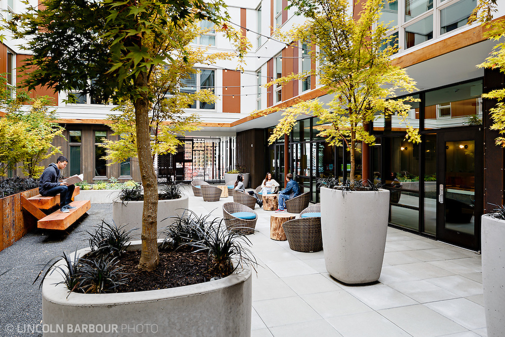 University House student housing apartment in Eugene, OR. Designed by Mahlum Architects. A modern design courtyard with several students engaging in conversation and another reading by himself.