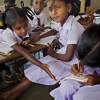 Pupils in a UNICEF-supplied Temporary Learning Space at Vadamunai Government Tamil Mixed School in Batticaloa District. <br /> <br /> When fighting between the LTTE and Colombo Government forced the displacement of the local Tamil community in 2007, the Vadamunai Government Tamil Mixed School in Batticaloa District was closed. Since reopening in January 2009, the school has six teaching staff for 88 pupils from Grades 1-9. Before closure,136 pupils studied at the school. Poor road-infrastructure and the remote location of the school means that many staff have to commute for more than three hours. Five classes are held in a UNICEF-supplied Temporary Learning Space. Four other classes are conducted outside, beneath trees. Many of the students suffer with the trauma and stress associated with those living in conflict situations. The staff must deal with these issues as well as the personal difficulties that they themselves suffer living in a conflict environment. To further antagonise an already difficult situation, the school suffers the very real danger of wild-elephant encroachment on their grounds. The school encourages gender-equality and has a meals program, providing some students their only square meal in the day. <br /> <br /> Photo: Tom Pietrasik<br /> Batticaloa District, Sri Lanka<br /> September 30th 2009