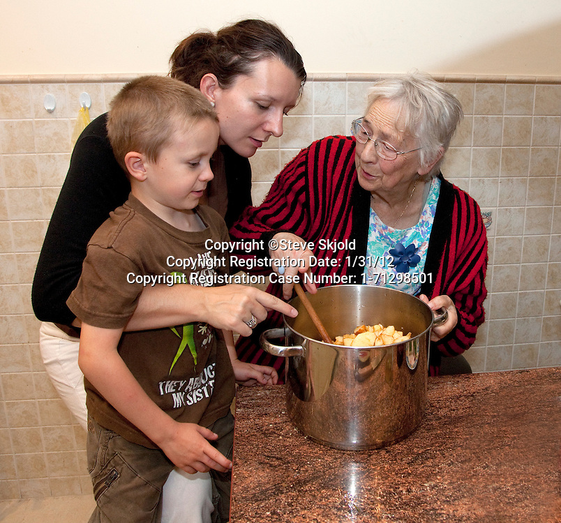 Polish Great grandmother and mom pointing out the fate of apple slices to young son age 6 Zawady Central Poland
