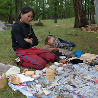 A reindeer-herding (Tsaatan) mother & her baby sell hand-made souveniers to tourists visiting Lake Hovsgol and the Horidal Saridag Mountains in Mongolia's Hovsgol National Park.