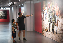 (170730) -- BEIJING, July 30, 2017 (Xinhua) -- Visitors look at a work displayed in a photo exhibition marking the 90th anniversary of the People's Liberation Army(PLA) in Beijing, capital of China, July 30, 2017.   (Xinhua/Chen Yehua)(clq) (Photo by Xinhua/Sipa USA)