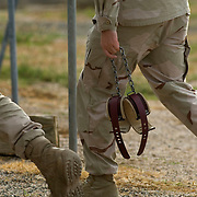 "A camp guard carries soft leg restraints outside Camp Delta at the detention facility in Guantanamo Bay, Cuba. Approximately 250 ""unlawful enemy combatants"" captured since the September 11, attacks on the United States continue to be held at the detention facility.(Image reviewed by military official prior to transmission)"