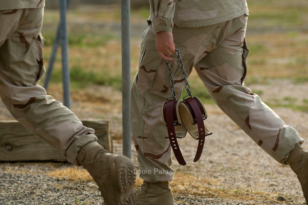 """A camp guard carries soft leg restraints outside Camp Delta at the detention facility in Guantanamo Bay, Cuba. Approximately 250 """"unlawful enemy combatants"""" captured since the September 11, attacks on the United States continue to be held at the detention facility.(Image reviewed by military official prior to transmission)"""