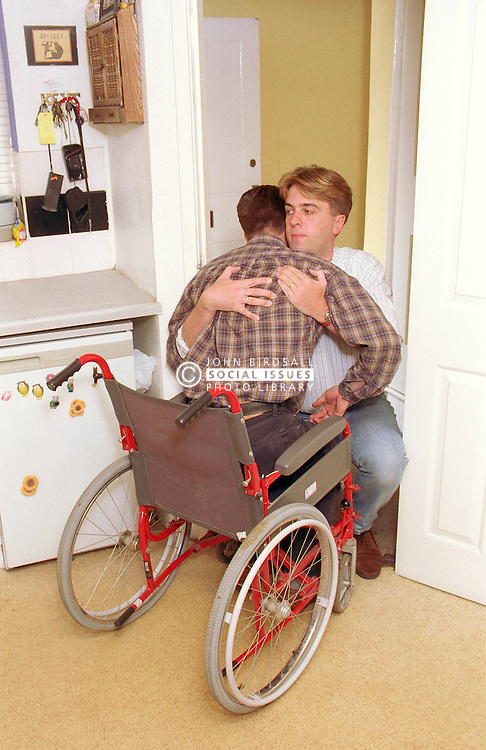 Carer assisting young wheelchair user,