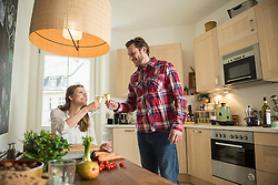 Couple celebrating with white wine in kitchen, Munich, Bavaria, Germany