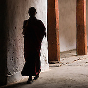 BHUTAN, WANGDUE PHODRANG DZONG (A dzong is a fortress and seat of civil and religious power -- Buddhism). A monk is walking past  a white wall in silhoutte. There are two pilars in the background. This monastery was consumed by fire and burned to the ground on June 24, 2012