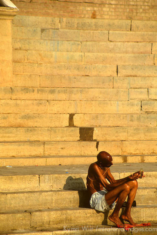 Asia, India, Uttar Pradesh, Varanasi. Scene of daily life along the ghats in the holy city of Varanasi on the Ganges River. A lone man in meditation faces the sunrise.