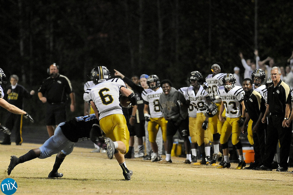 The sidelines react as Spiders linebacker Landon Loukos (6) runs back an interception during the Concord Spiders at West Rowan Falcons high school football game on October 23.