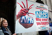 Tens of thousands of health workers, activists and members of the public protested against austerity and cuts in the NHS National Health Service on March 4th 2017 in London, United Kingdom. A man and a woman hold a banner which shows  a heart and the words The government is ripping the heart out of the NHS, why arent you angry?,