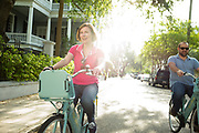 CHARLESTON, SC – MAY 11, 2017: Two people ride bikes from the Holy Spokes Charleston Bike Share sponsored by the Medical University of South Carolina.