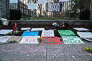 Protest signs, flowers, and a Black Lives Matter flag are displayed at the Allen Street Gates in State College, Pennsylvania on March 19, 2021. The 3/20 Coalition organized a protest and march to mark the second anniversary of Osaze Osagie being shot and killed by State College police at his apartment. (Photo by Paul Weaver)