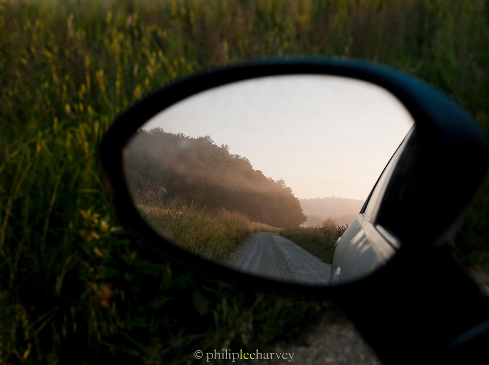 A country track on a misty morning in a car wing mirror, near the villag of Solomeo, Umbria, Italy