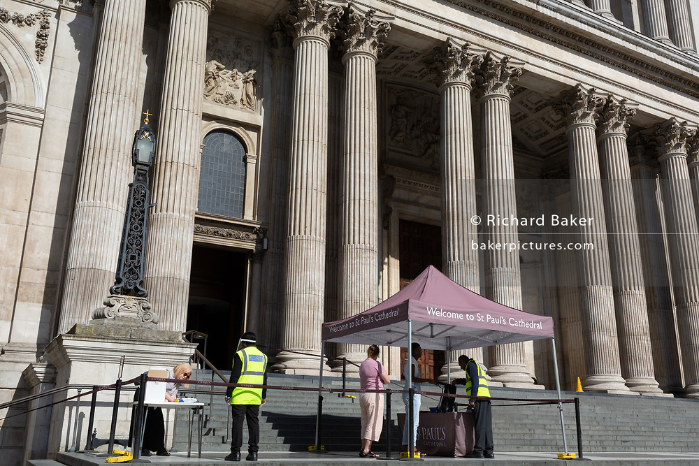 Visitors to St. Paul's Cathedral undergo security checks, filling out their contact details and other personal information during the Coronavirus pandemic in the City of London, on 20th July 2020, in London, England. Contact details may be used to track and trace those who may have been in close proximity with anyone revealed to be infected with Covid.