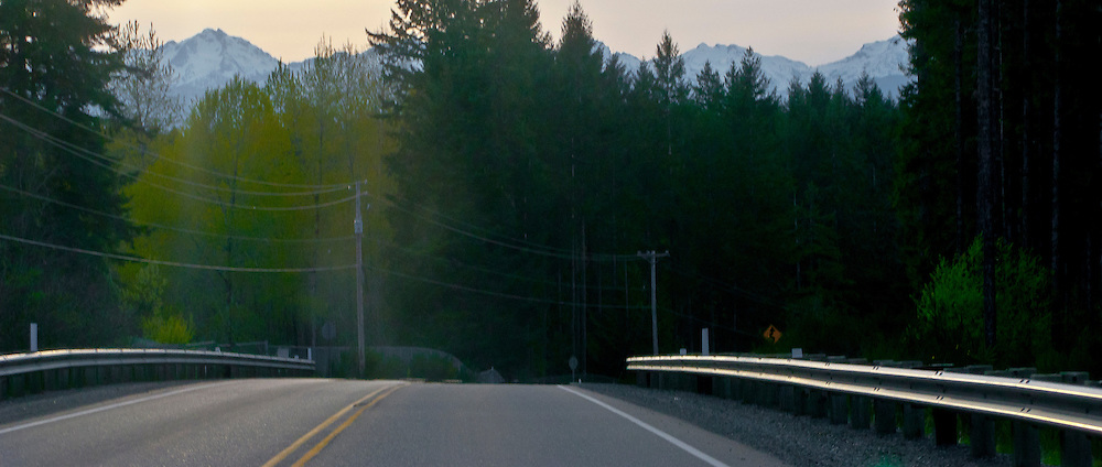scene along a cross country trip with in a classic Mini Cooper auto - rural road in Mason County, WA with guardrails, pavement and power line prominent in the image