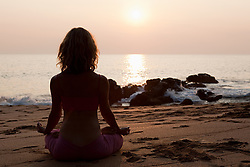 Jul. 25, 2012 - Woman practicing yoga on beach at sunset (Credit Image: © Image Source/ZUMAPRESS.com)
