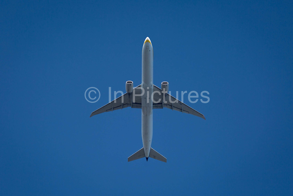 A Boeing 777-35RER jet airliner with Jet Airways flies overhead in blue skies on its flight-path into London Heathrow airport, on 8th August 2018, in London, England.