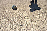 A sliding rock and man on The Racetrack Playa in a remote part of Death Valley National Park, California, USA
