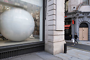 Large white ball in the window of a building in Mayfair on 28th January 2021 in London, United Kingdom. This huge scale sphere interacts with passing people.