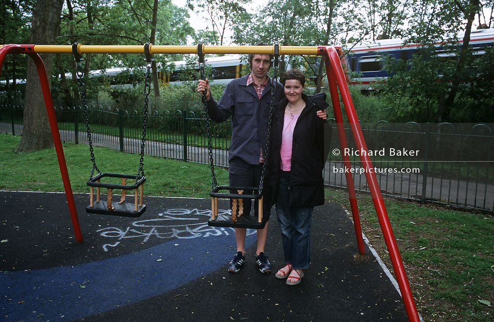 Smiling but childless couple stand by two empty childrens' park swings as a commuter train passes behind in south London.