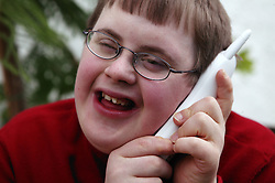Teenage Downs Syndrome boy laughing on the telephone,